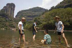 Tourists stand in shallow water along the Nine Bends River in Wuyishan in eastern China's Fujian province.