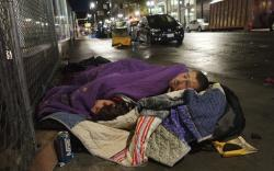 In this Sept. 18, 2017, file photo, two people sleep on a street in downtown Portland, Ore.