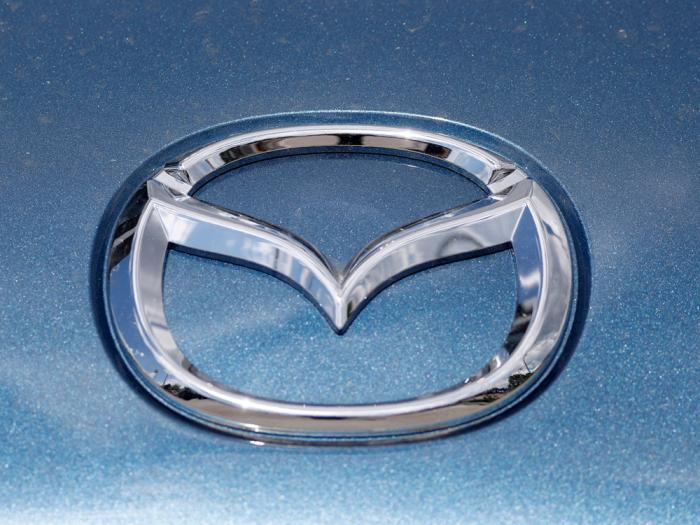 In this June 14, 2020, photograph, a Mazda company logo shines on the front of an unsold 2020 Miata at a Mazda dealership in Littleton, Colo.