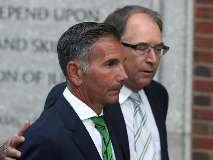 In this April 3, 2019 file photo, clothing designer Mossimo Giannulli, foreground, departs federal court in Boston after facing charges in a nationwide college admissions bribery scandal