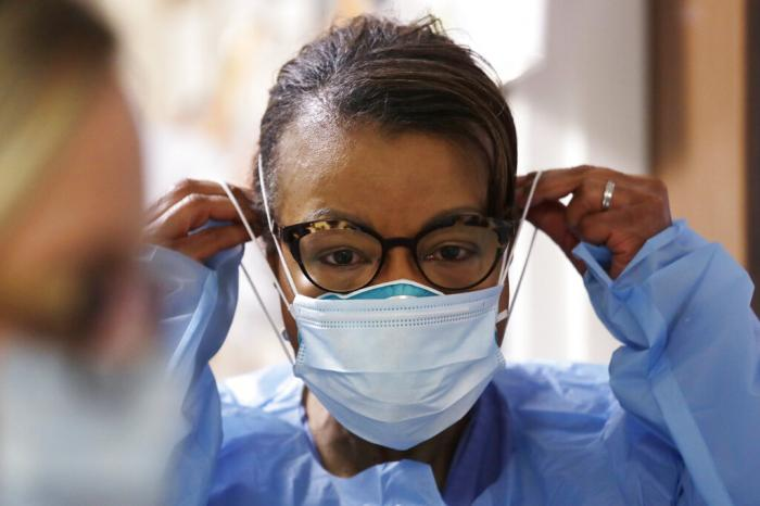 A respiratory therapist pulls on a second mask over her N95 mask before adding a face shield as she gets ready to go into a patient's room in the COVID-19 Intensive Care Unit at a hospital in Seattle.
