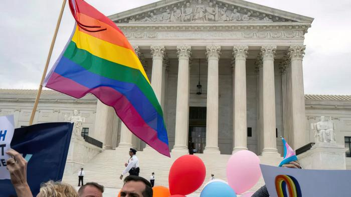 LGBT supporters wave their flag in front of the U.S. Supreme Court on Oct. 8, 2019, in Washington.