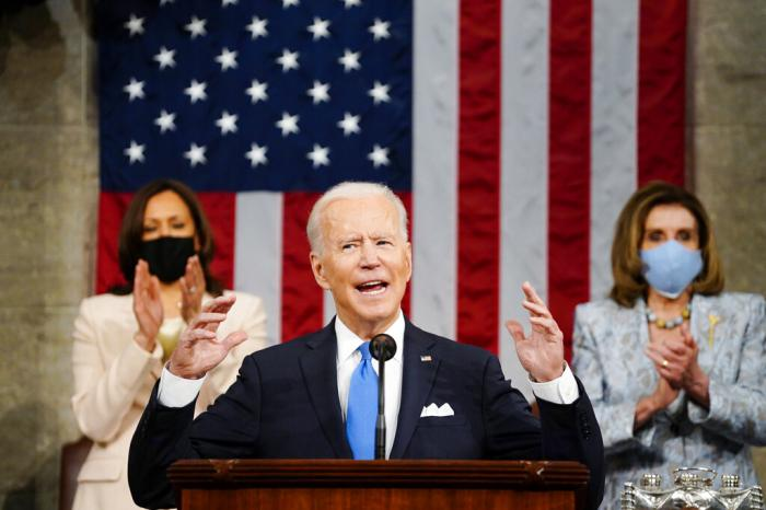 Vice President Kamala Harris, and House Speaker Nancy Pelosi of Calif., stand and applaud as President Joe Biden addresses a joint session of Congress.
