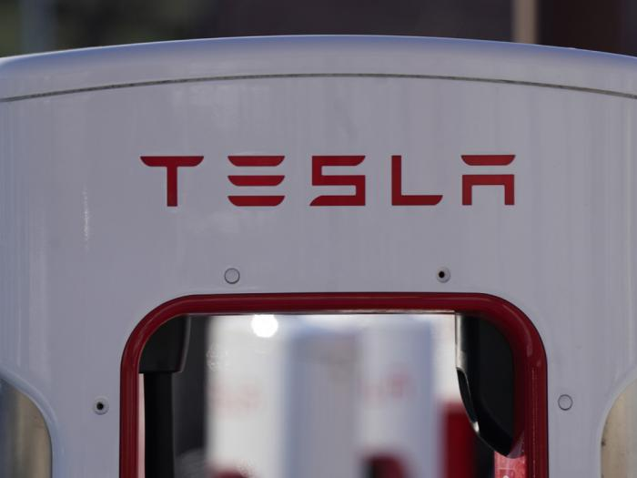 The company logo is shown at the top of a supercharger for Tesla automobiles near shops Feb. 25, 2021 in Boulder, Colo.