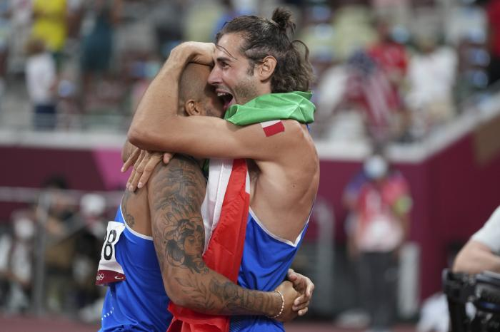 High jump gold medalist Gianmarco Tamberi, right, of Italy, congratulates compatriot Lamont Marcell Jacobs, after he won the final of the men's 100-meters at the 2020 Summer Olympics.